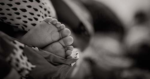 person grayscale photo of baby's feet baby