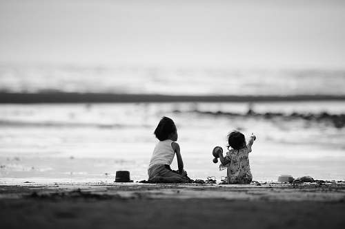 person grayscale photography of two girls sitting on shore black-and-white