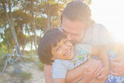 person man kissing child during golden hour hug