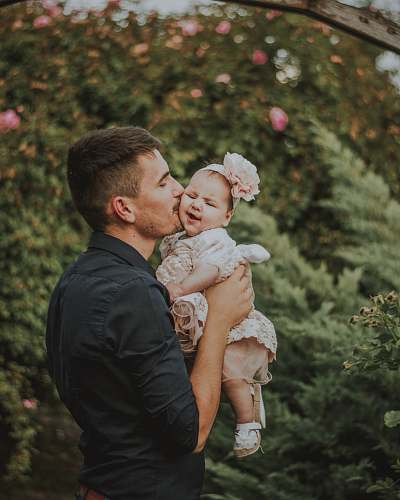 photo person men holding a baby near plants during daytime clothing free for commercial use images