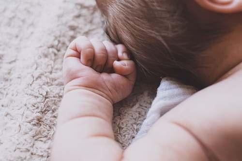 person newborn baby lying down on brown blanket people