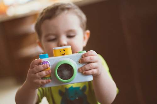 person toddler holding white camera toy people