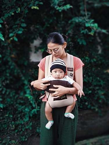 person woman holding baby beside green plants apparel