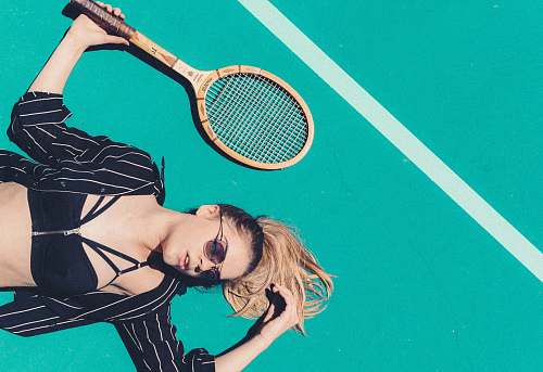 people woman lying on floor holding tennis racket racket