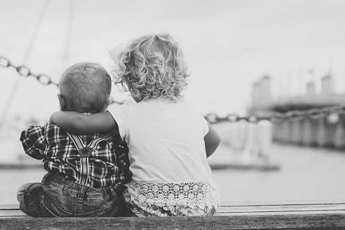 black-and-white grayscale photography of two children sitting on ledge grey