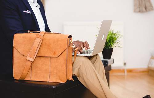 work person using MacBook Pro beside brown leather briefcase business