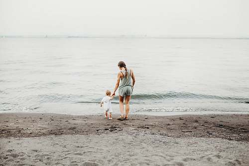 photo person woman and baby walking on gray sand seashore during daytime human free for commercial use images