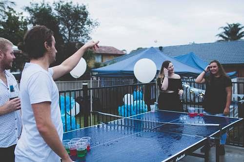 human woman versus man playing beer pong under cloudy sky ping pong