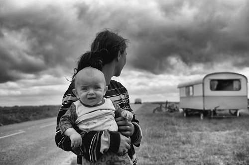photo black-and-white gray scale photography of woman carrying baby looking at camper trailer people free for commercial use images