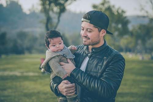 photo apparel man wearing black leather jacket holding baby clothing free for commercial use images