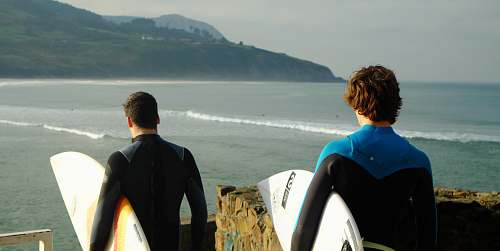 photo water two male wearing wetsuits holding surfboards standing nearby each other on top of hill with view of beach below surfboard free for commercial use images
