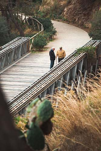 photo human two men standing on bridge banister free for commercial use images