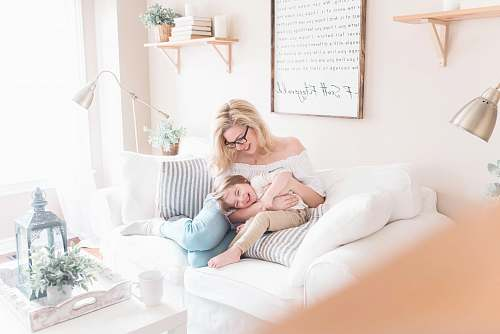 human woman and baby sitting on white sofa furniture