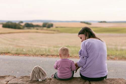 human woman and child sitting next to each other apparel
