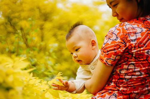 photo human woman in orange, white, and black floral short-sleeved shirt holding baby baby free for commercial use images