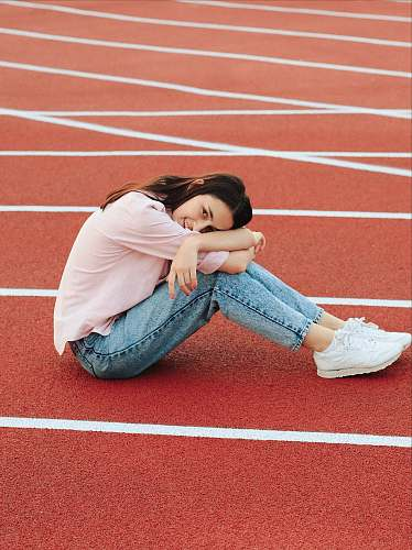 photo human woman sitting on track field running track free for commercial use images
