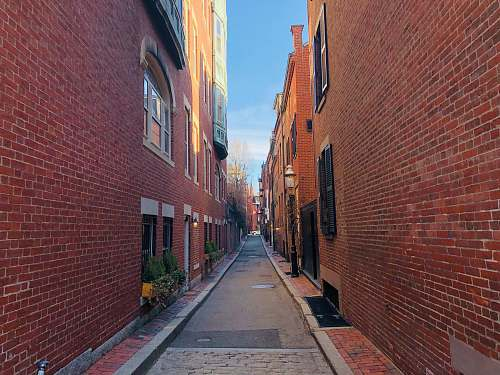 photo city empty pavement in between brick building during daytime street free for commercial use images