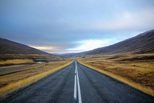 freeway landscape photography of black asphalt road with white line surrounded by brown grass field during daytime iceland