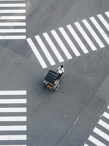 asphalt man pulling carriage crossing pedestrian tarmac