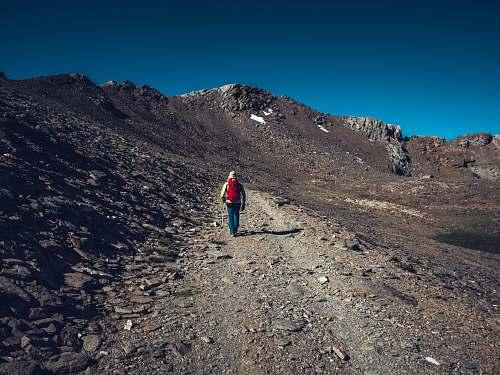 gravel man standing beside rock mountain dirt road