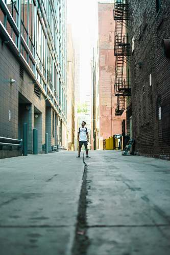 photo city man standing in middle of road during daytime urban free for commercial use images