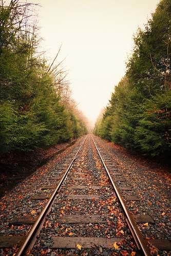 gravel train rail during daytime dirt road