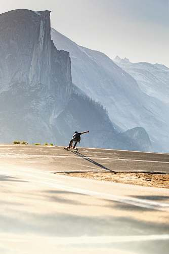 photo mountain man riding longboard cliff free for commercial use images