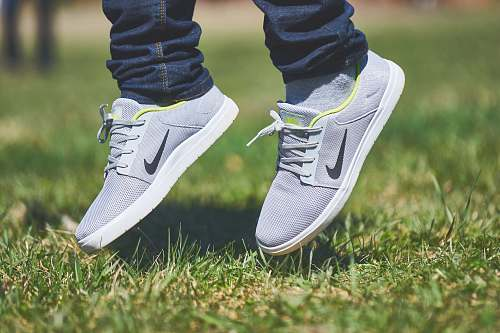 photo shoe pair of gray Nike low-top sneakers hanging on green grass spring free for commercial use images