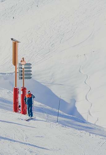 skiing man in blue jacket holding ski poles standing near red and brown post piste