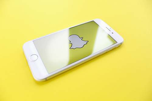 snapchat silver iPhone 6 on top of yellow wooden surface app