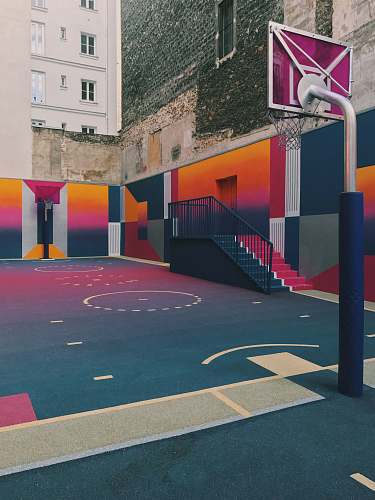 basketball black, purple, and orange basketball court beside concrete buildings at daytime basketball court