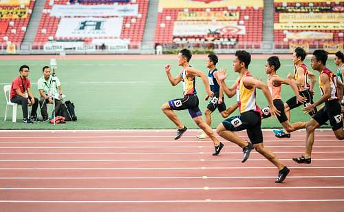 sports group of men running in track field people