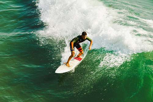 photo sea man on surfboard surfing against waves surfing free for commercial use images