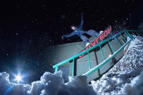 sports man riding on snowboard at nighttime nature