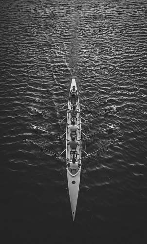 team people riding boat on body of water black-and-white