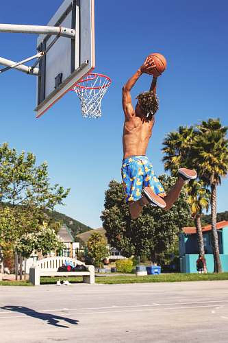 sports person dunking ball under blue sky during daytime basketball