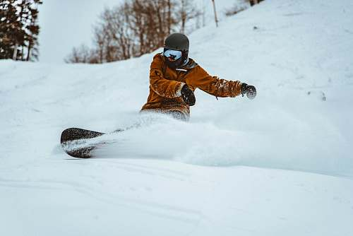 snowboarding photography of person playing snowboarding during daytime outdoors