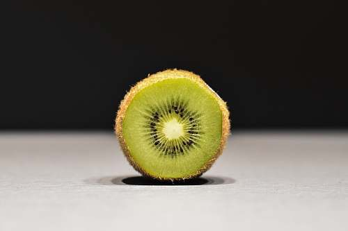 sports sliced kiwi on white surface ball