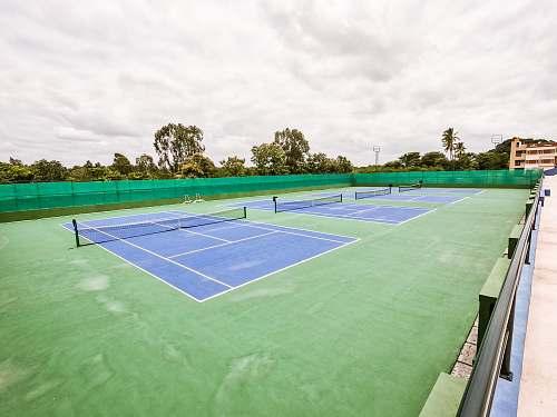 sports three blue lawn tennis courts tennis court