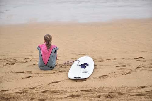 surfboard woman sitting on shore beside surfboard near sea sea