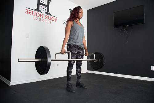 sports woman standing and lifting barbell working out
