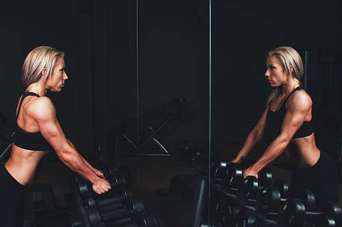 people woman wearing black top top holding black dumbbells standing in front of mirror fitness