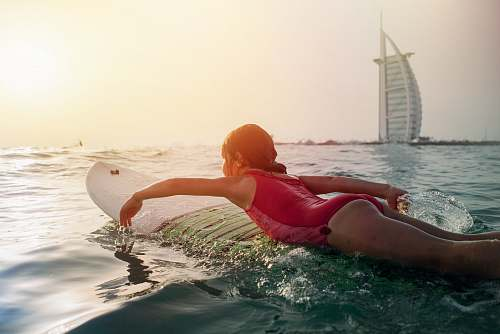 photo surfboard girl on top of white surfboard beside Burj Al Arab sport free for commercial use images
