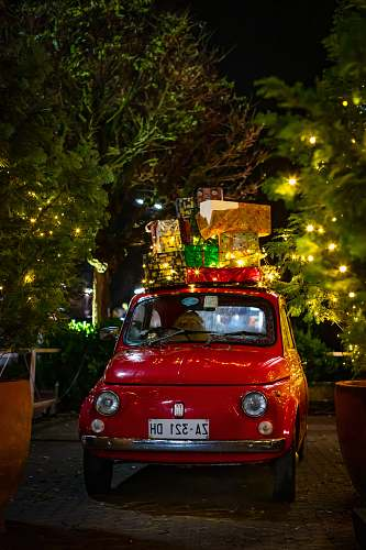 vehicle classic red FIAT 500 with christmas boxes on top car