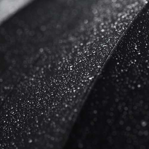 black-and-white Macro shot of tiny droplets of water on a black surface water drop