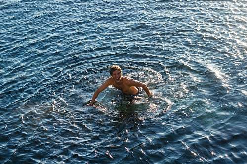 photo swimming topless man swimming in body of water human free for commercial use images