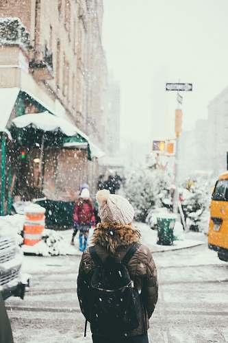 snow woman in brown jacket standing beside road upper west side