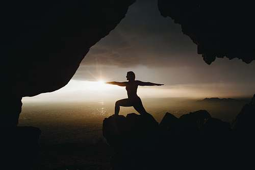 silhouette silhouette of person in yoga post on top of cliff during sunset sunset