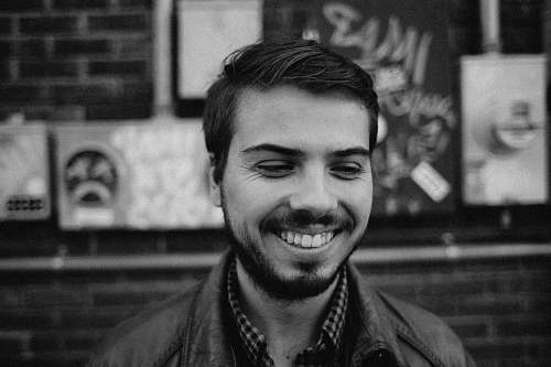 person grayscale of man smiling human