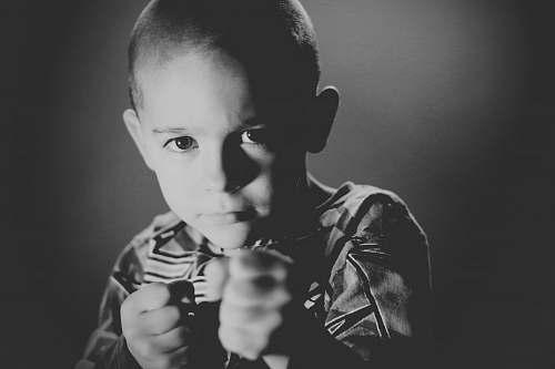 human grayscale photo of boy wearing crew-neck top grey